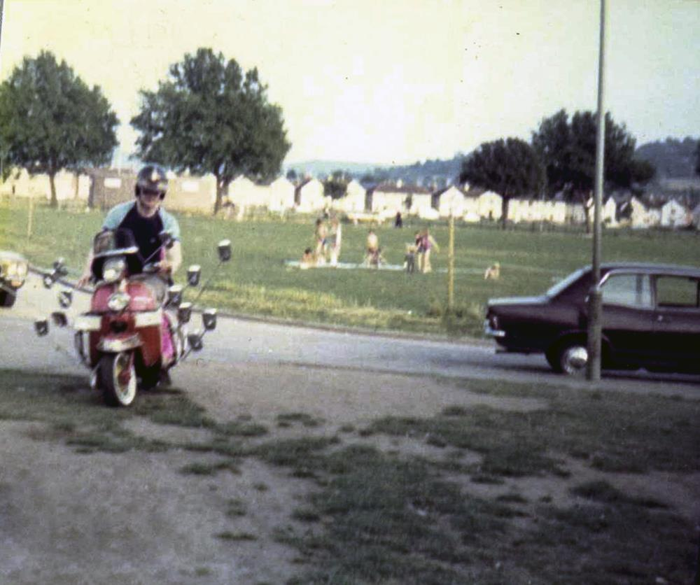 Man riding a Lambretta scooter with pink furry side panels