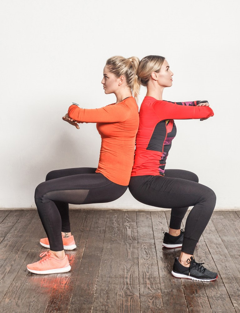 Two ladies doing a wall sit by leaning on each other - how teamwork can help with a monthly fitness challenge