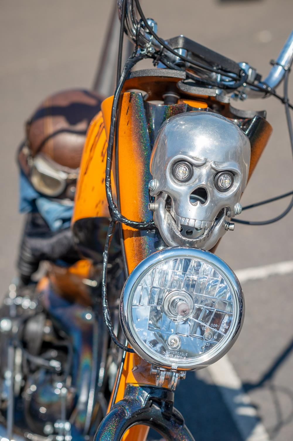 Close-up of front headlight and skull feature on an orange Lambretta chopper scooter