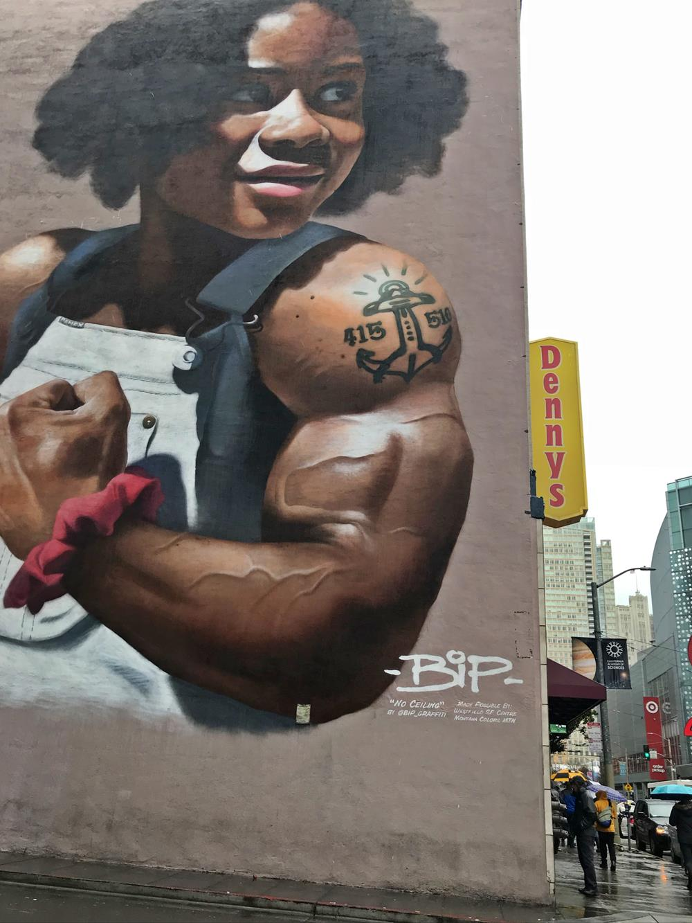 Five story image of a young girl with unnaturally large muscles, seen on a San Francisco street art tour