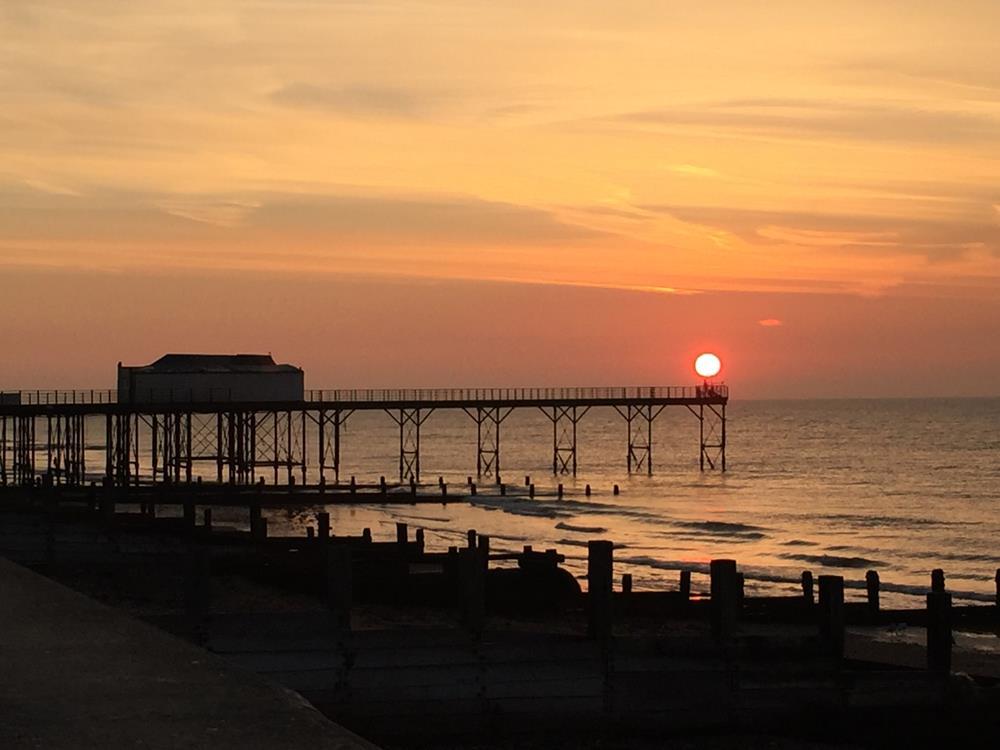 View of Bognor pier as the sun is rising in orange skies