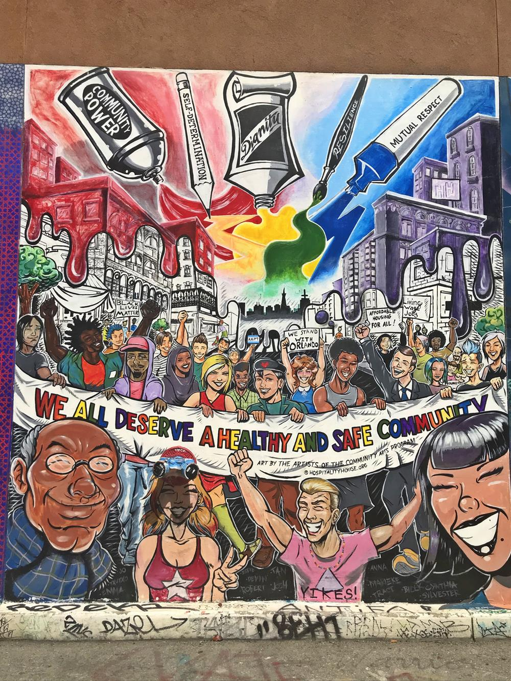 Brightly-coloured street art featuring people celebrating and a banner which says We All Deserve A Healthy And Safe Community