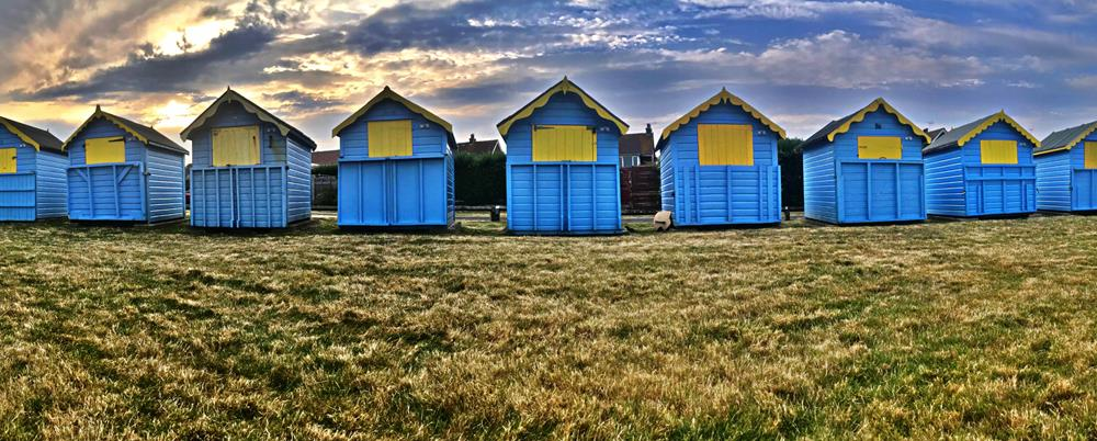Bognor's best Instagram sports include these blue beach huts with colourful clouds in the background