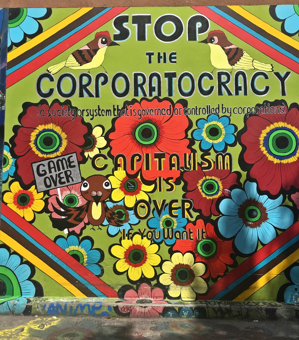 Street art featuring flowers and text Stop The Corporatocracy