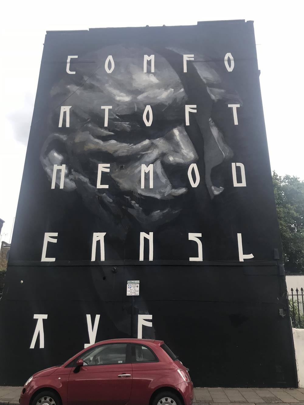 Giant wall mural on the side of a building in Hackney with a skull and the words Comfort Of The Modern Slave