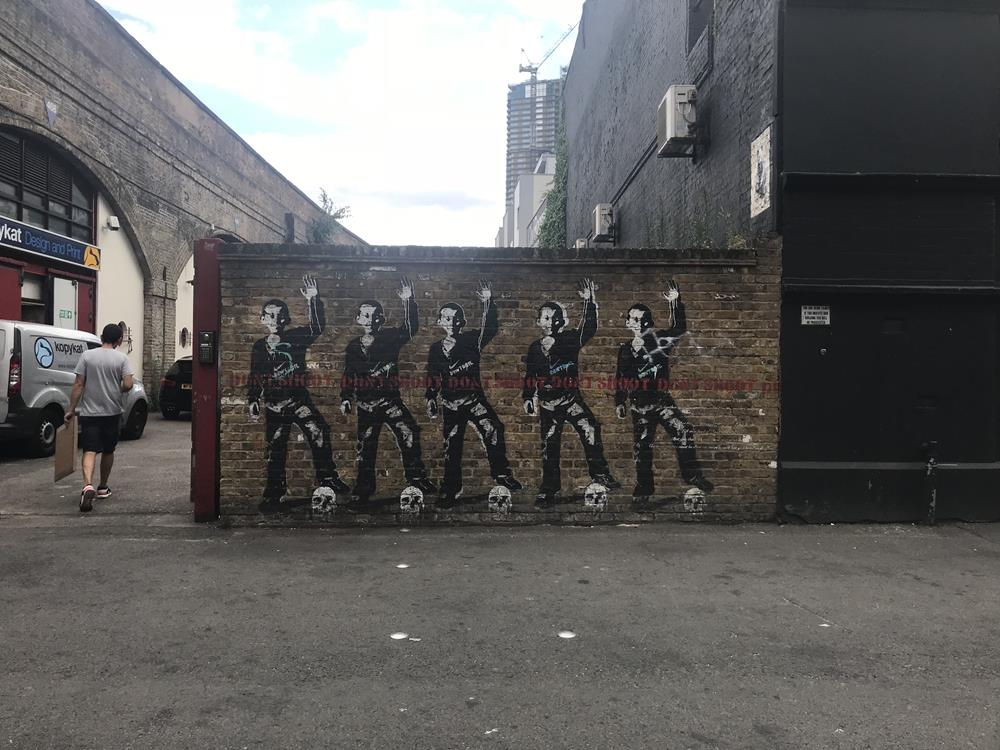 Street art by Bambi featuring stencilled football players saying 'don't shoot' with skulls as footballs