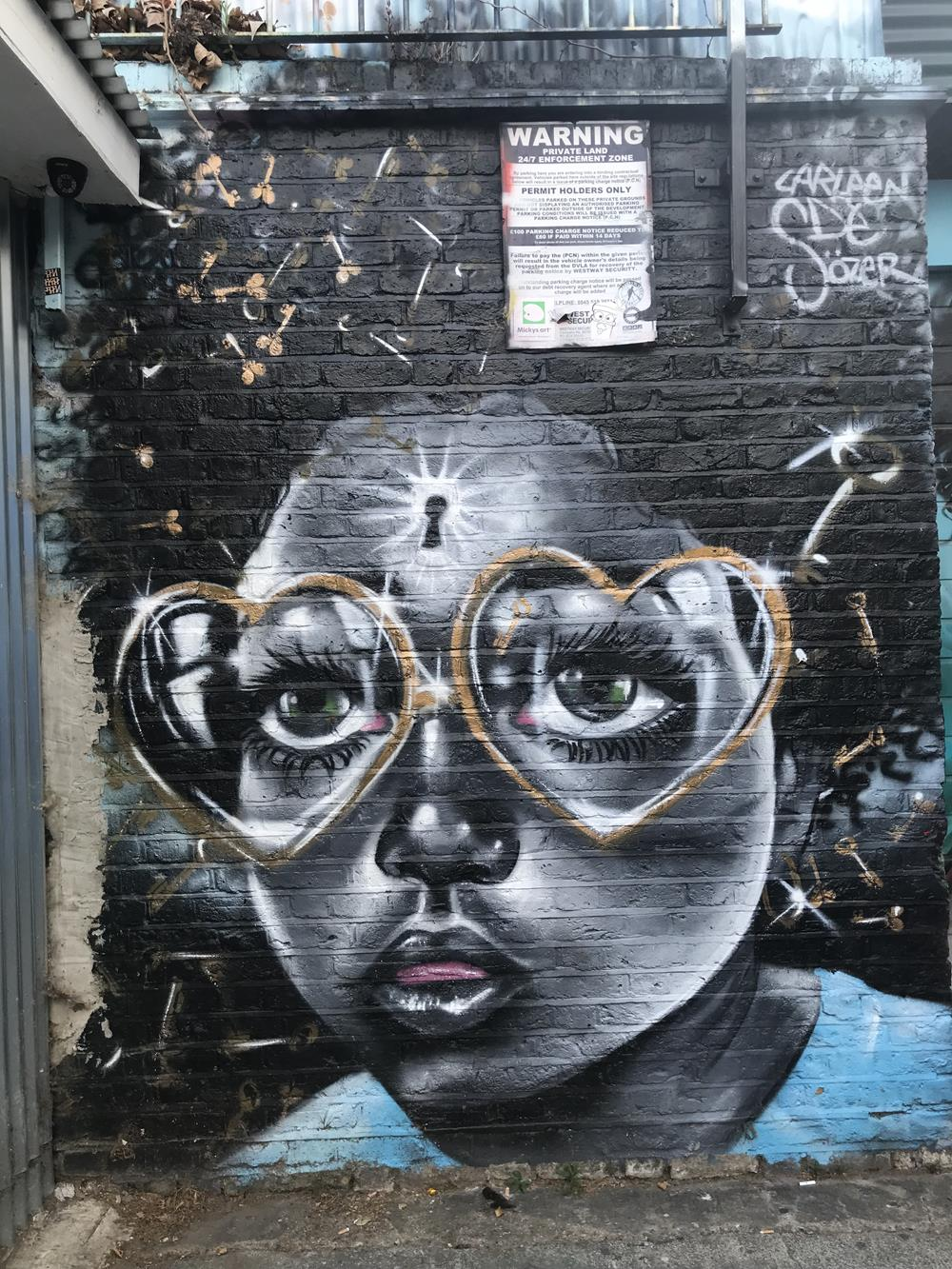Image of a black lady with large glasses in Brick Lane