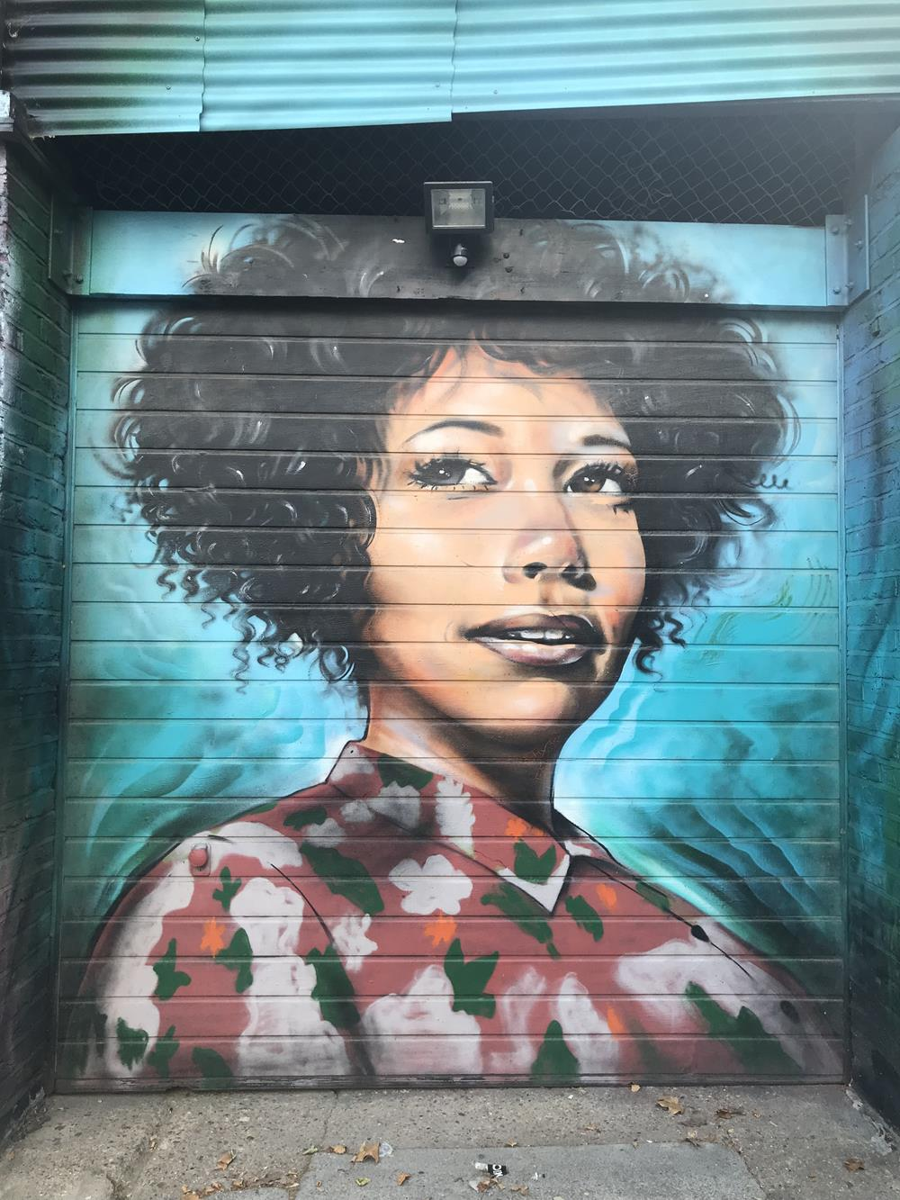 Head and shoulders portrait of a woman street art in a Brick Lane alley