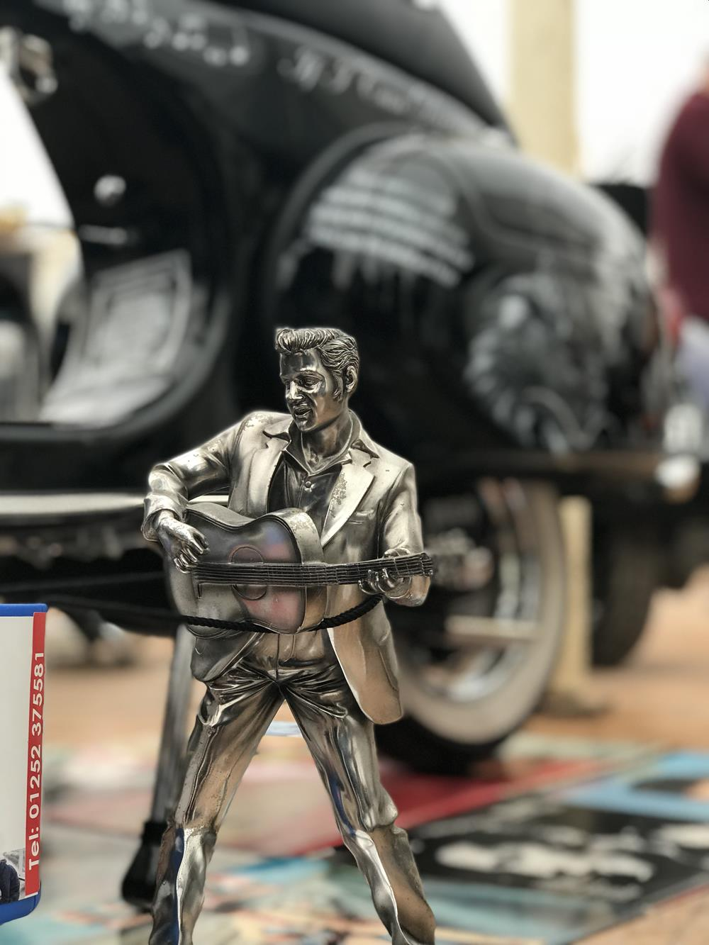 A mini statue of Elvis with Elvis-themed scooter in the background
