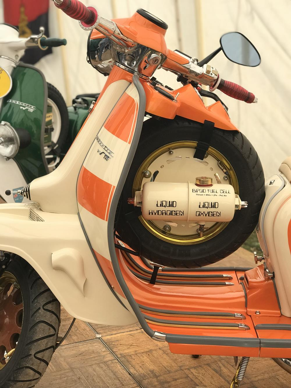Orange and cream Lambretta with spare wheel behind the legshields and liquid hydrogen cannister