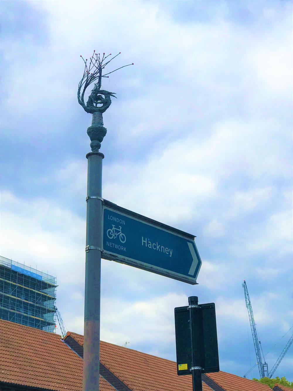 Sculpture on top of a street sign in Hackney