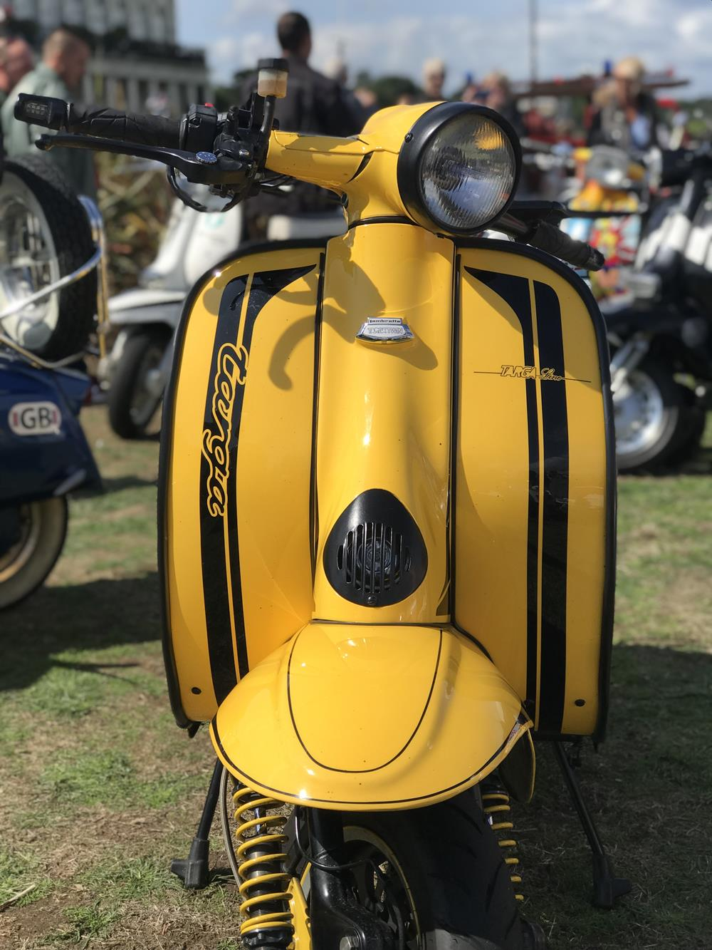 Yellow Lambretta with black stripes on the legshields