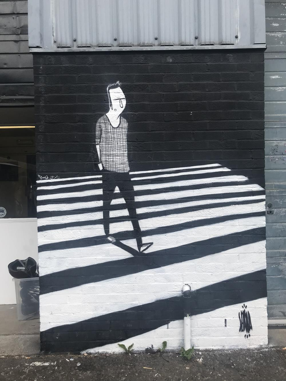 Wall mural featuring a man walking over a zebra crossing