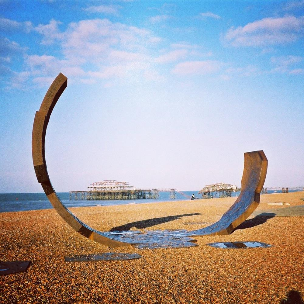 Charles Hadcock sculpture Passacaglia, framing Brighton's West Pier perfectly