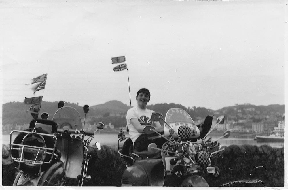 Norrie Kerr sitting on a Vespa scooter with flyscreen, lights and mirrors.