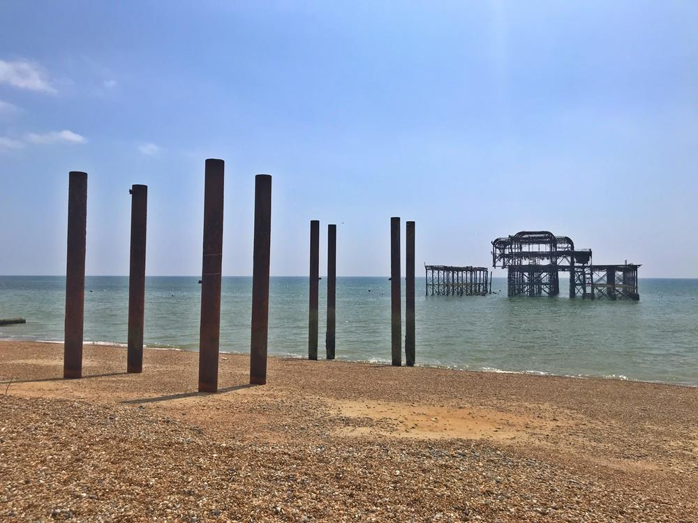 View of Brighton's West Pier from the shore with cast iron supports on the beach