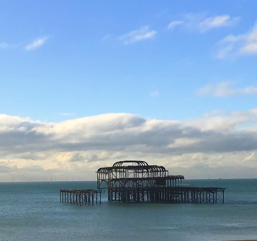 View of Brighton's West Pier from the shore on a sunny day with clouds and blue sky above