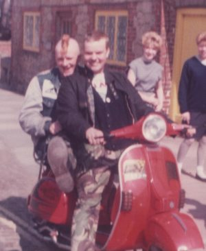 Dizzy on a red Vespa PX with Jamie on the back