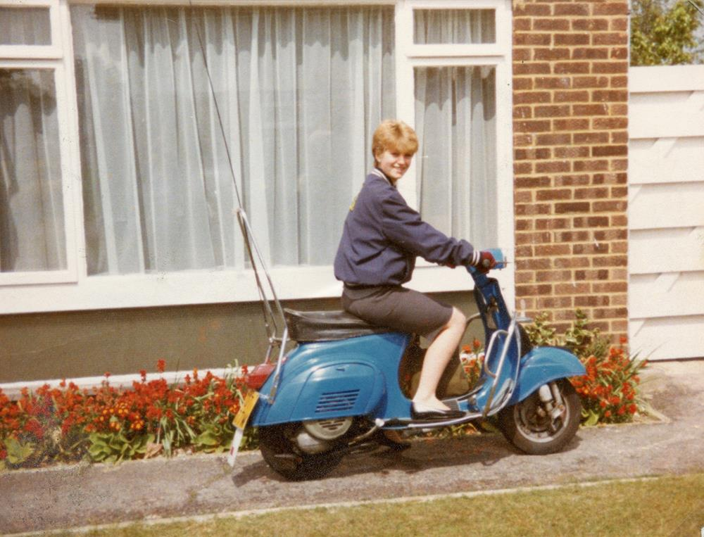 Ali Richards sitting on her blue Vespa 50 Special