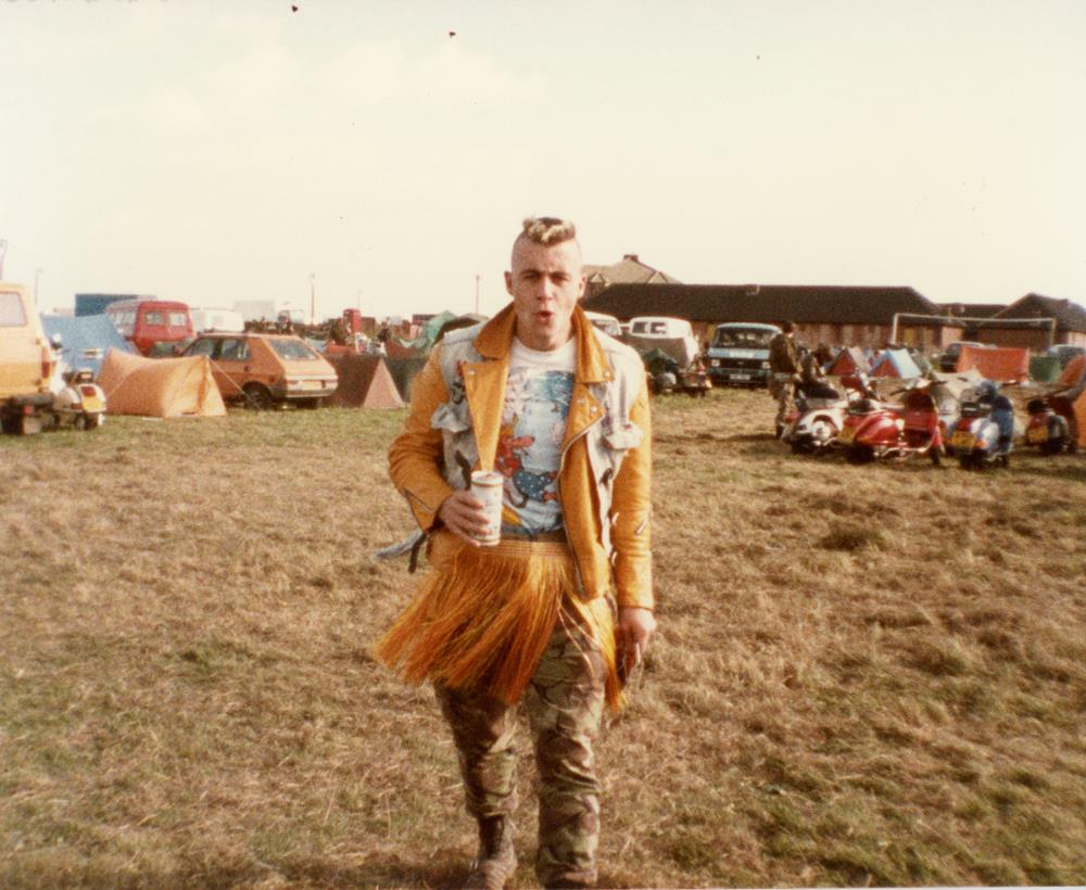 Mick Hames showing 80s scooter fashion by wearing a grass skirt, King Kurt t-shirt, camouflage trousers and denim cut-off over a leather jacket.