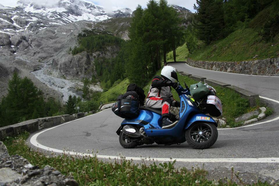 Iggy Grainger riding a blue Vespa GTS on a hairpin bend on the Stelvio Pass