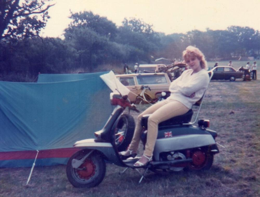 Sandra Smith next to a tent, sitting on a Lambretta, at Smallbrook Stadium in 1983