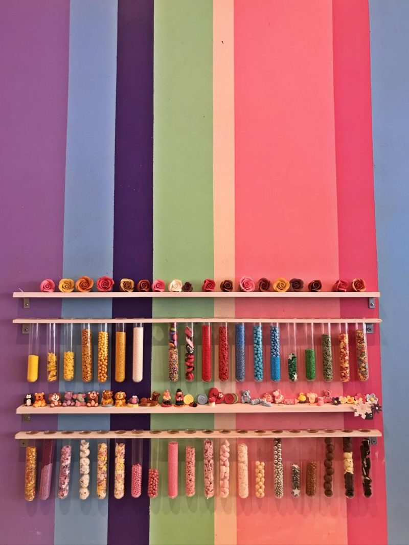 Stripey wallpaper with tubes holding various sprinkles and sweets to put on top of an ice cream