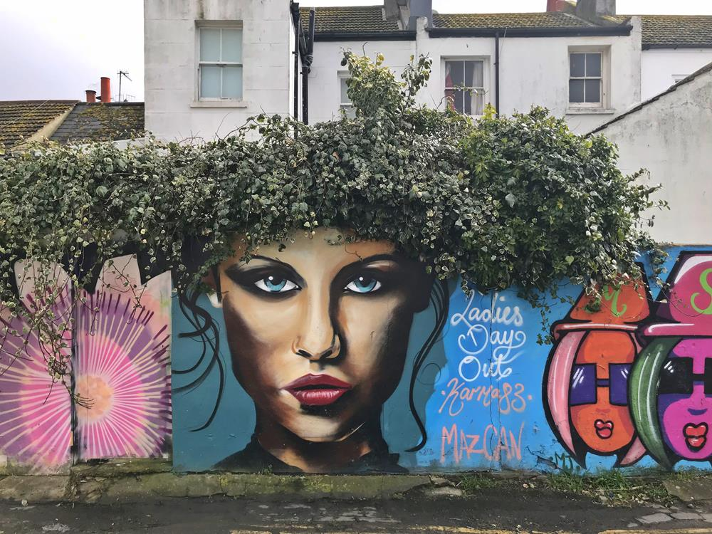 Girl with bush for hair, a wall mural by Mazcan in Brighton, one of the most iconic pieces of street art there