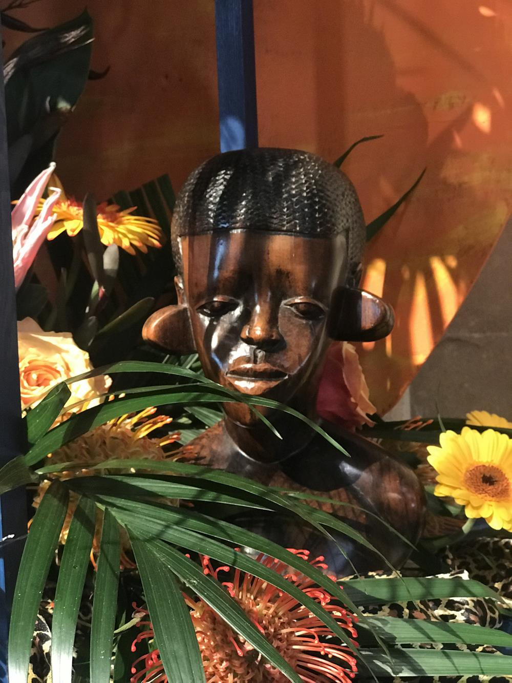 Wooden Africal statue in floral arrangement