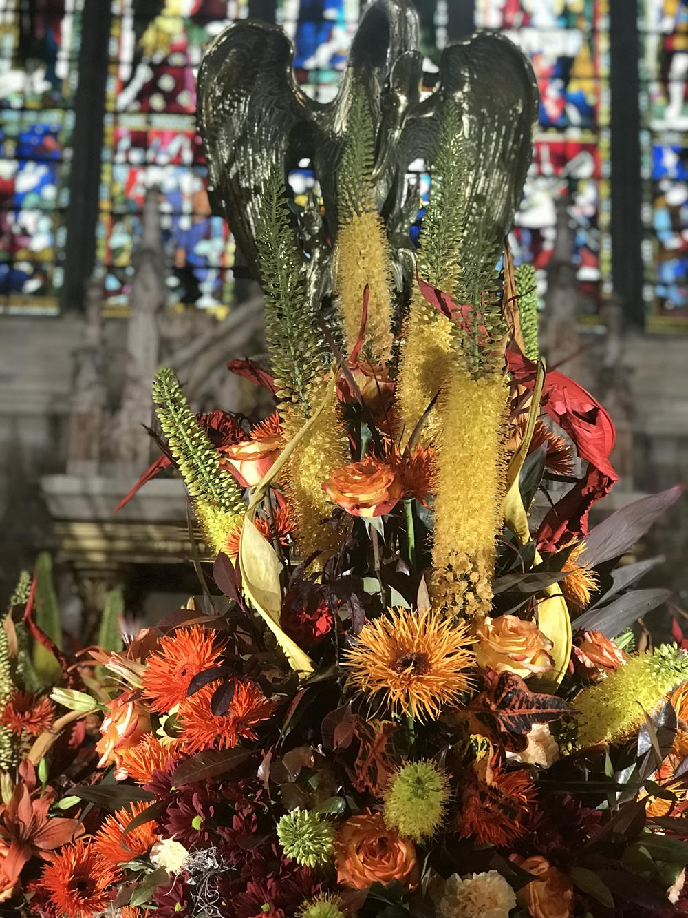 Floral display in front of stained glass window at Chichester cathedral