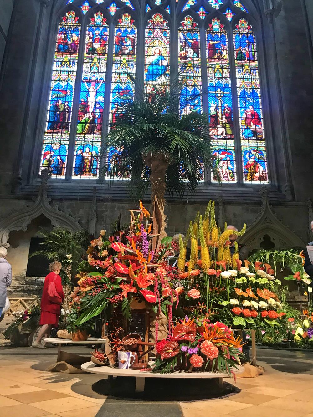 Flower display under stained glass window at Chichester Cathedral