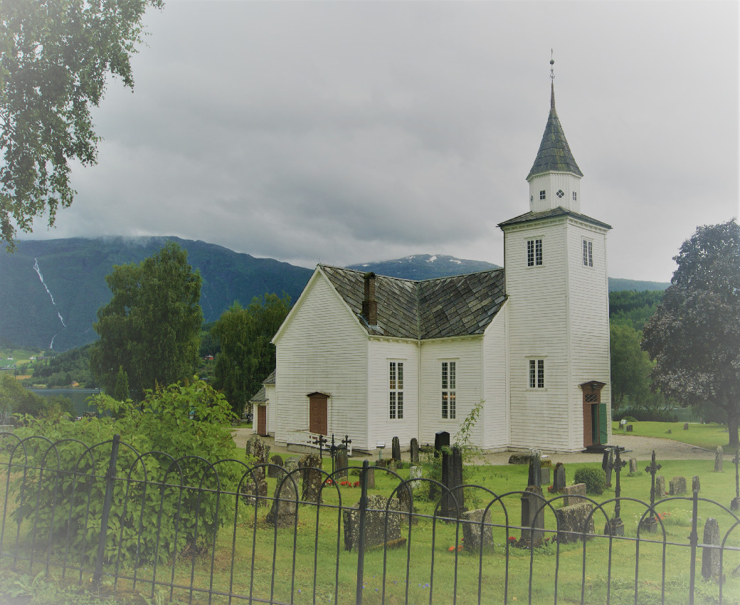 Ulvik church, which is painted white and made of wood, surrounded by gravestones
