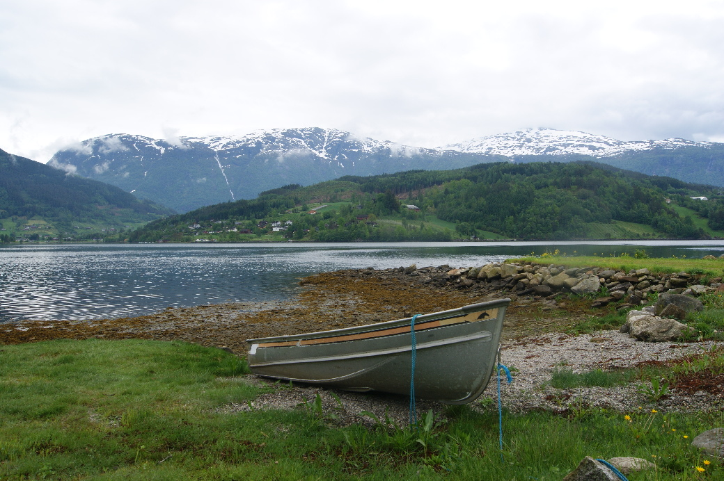 A small rowing boat in the foreground with Handangerfjord behind and snow-topped mountains in the distance