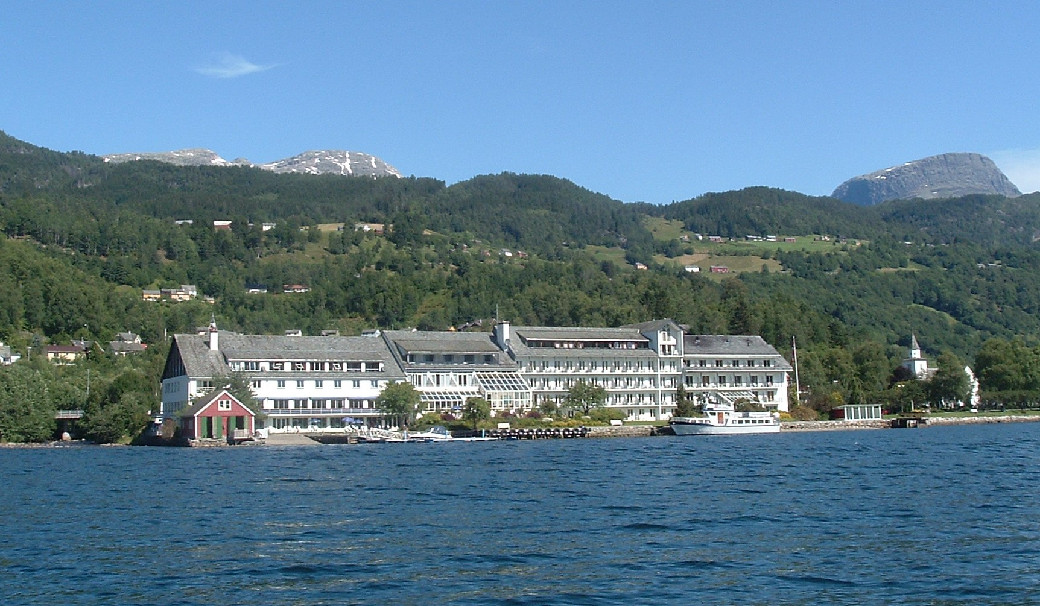 The Brakanes Hotel which overlooks the fjord with green mountains in the background