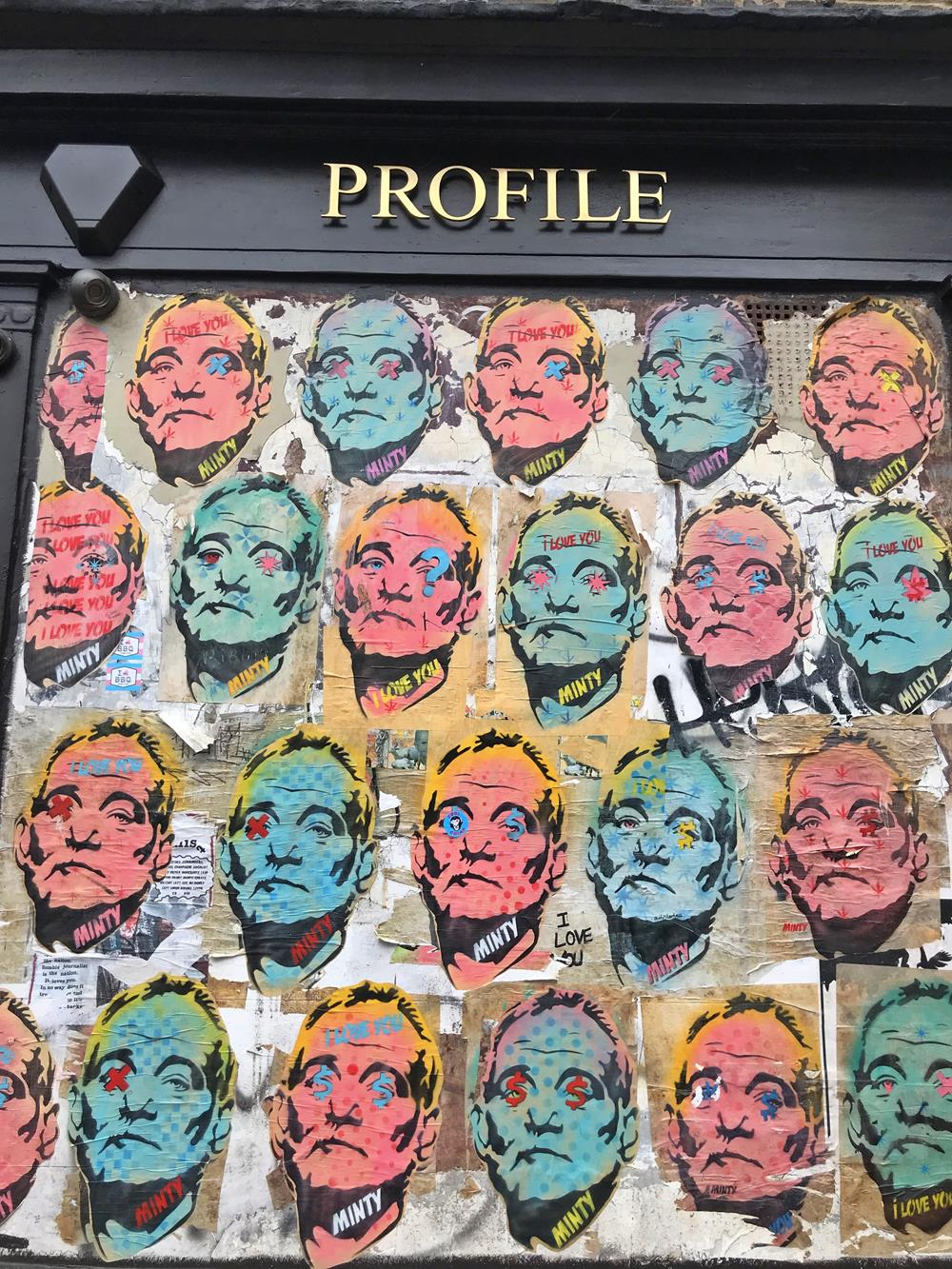 Multiple paste up images by Minty on the shop front of Profile in Brighton