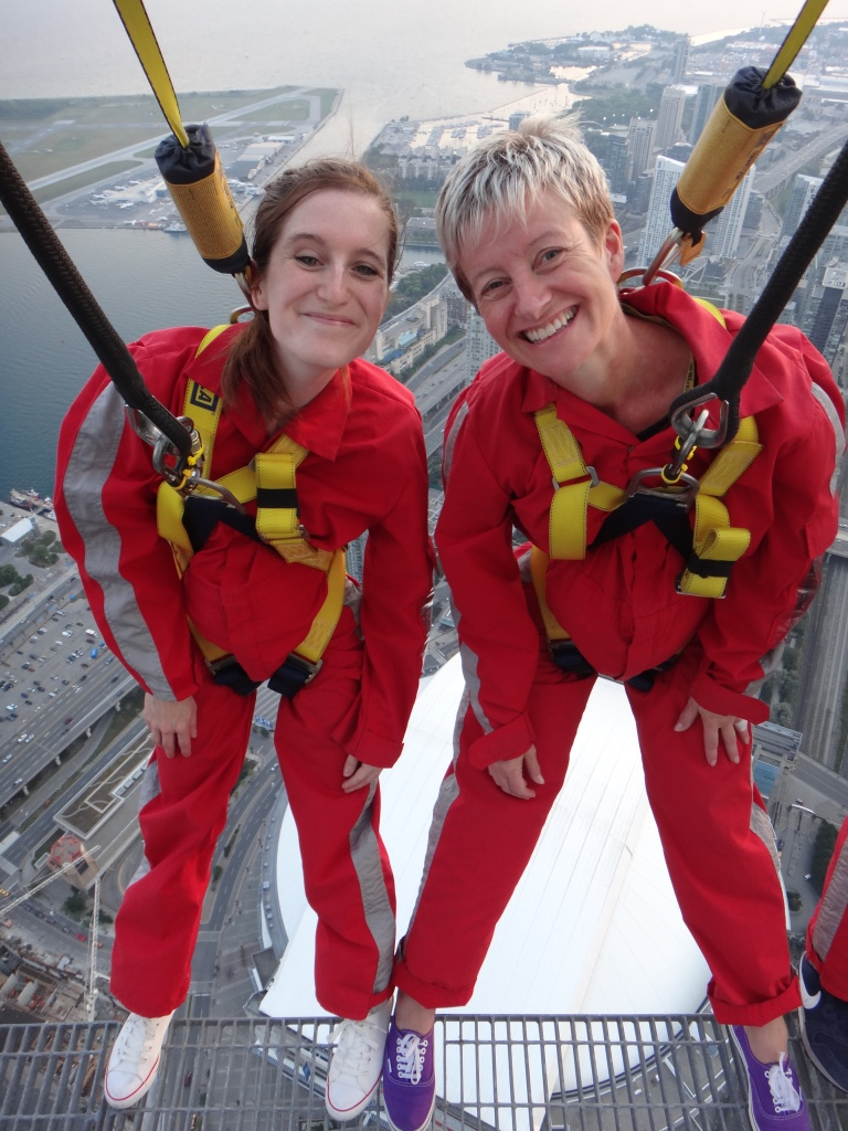 Two participants leaning backwards at the top of the CN Tower in Toronto