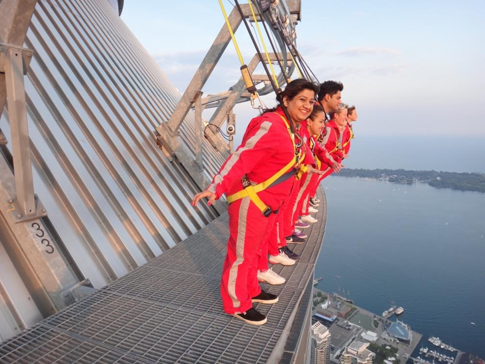 Side view of CN Tower Edge Walk participants leaning off the edge of the walkway
