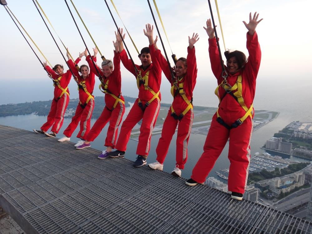 Six CN Tower Edge Walk participants leaning backwards with their hands in the air on the Edge Walk walkway