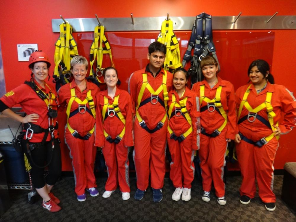 Edge Walk participants in red jumpsuits with harnesses