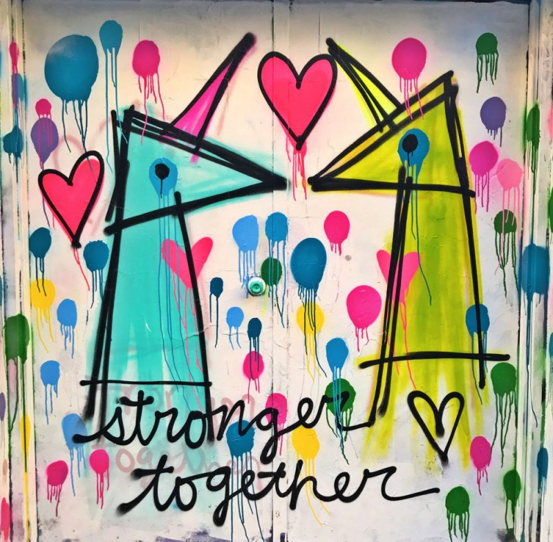 A bright and colourful piece with turquoise, pink green and yellow shapes with the words Stronger Together and pink hearts
