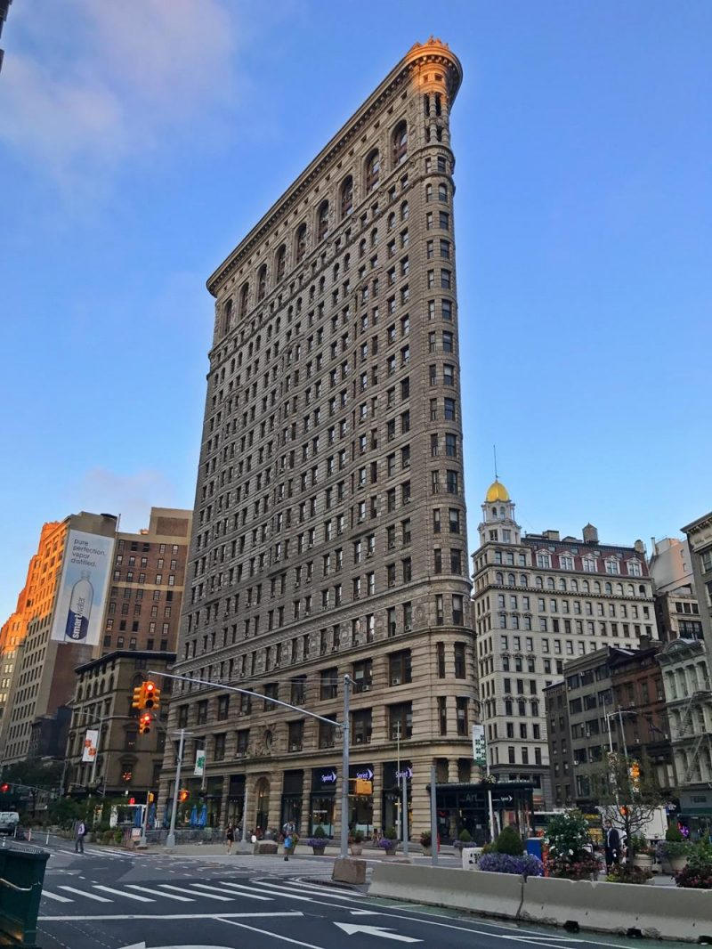 view of the flatiron building from the street with blue skies in the background