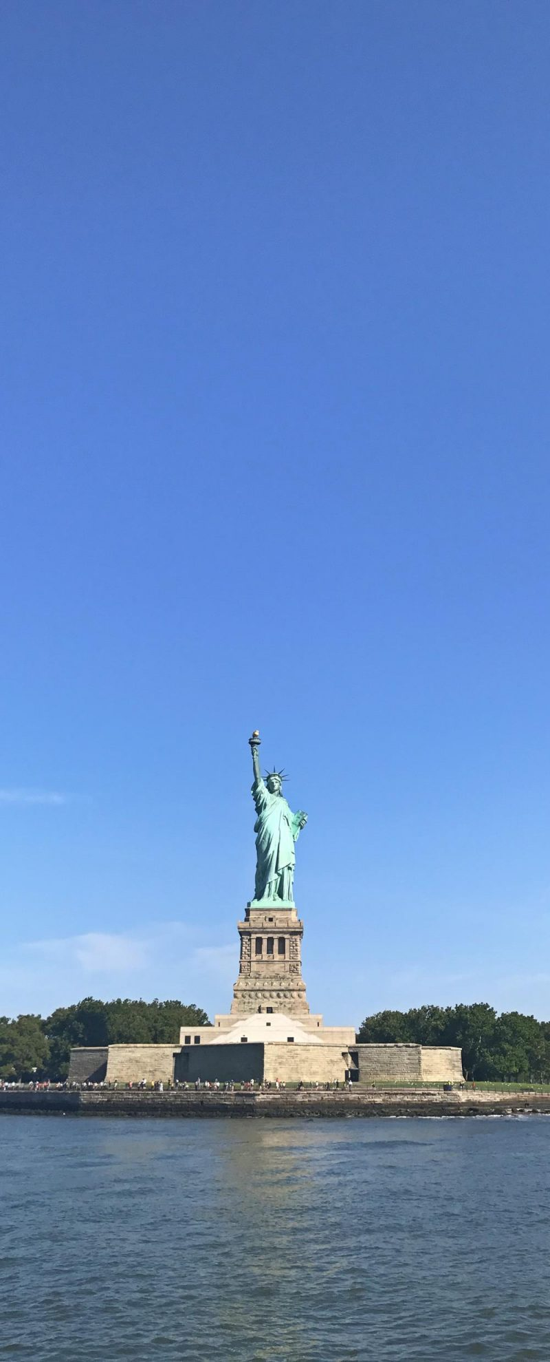 The statue of liberty with bright blue sky in the background