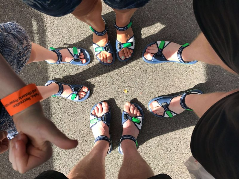 Four pairs of feet wearing ugly sandals