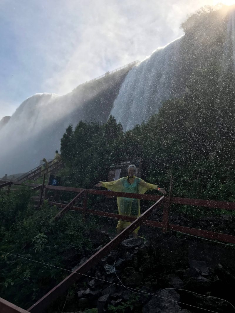 picture of the author with the falls in the background with what looks like rain but is in fact the spray from the falls