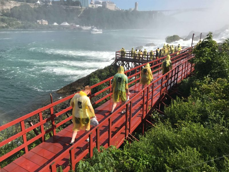 People walking over a boardwalk, wearing yellow ponchos, with spray from the falls in the background