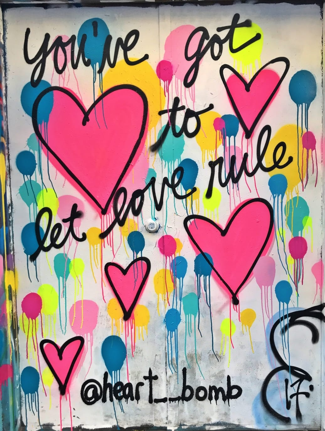 A vibrant graffiti design with pink hearts and blue, yellow and green spots with the words You've Got To Let Love Rule
