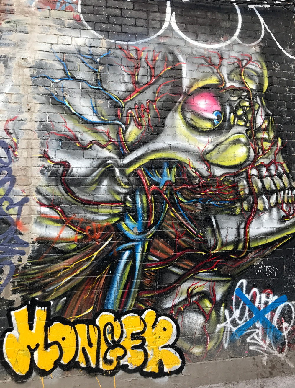 Graffiti of a skull with blue veins and red arteries coming out of the side and top