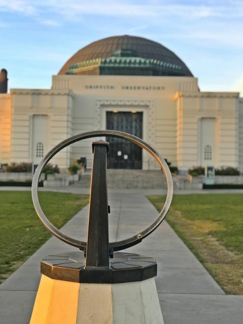 The sundial at the front of Griffith Observatory with the main building in the background