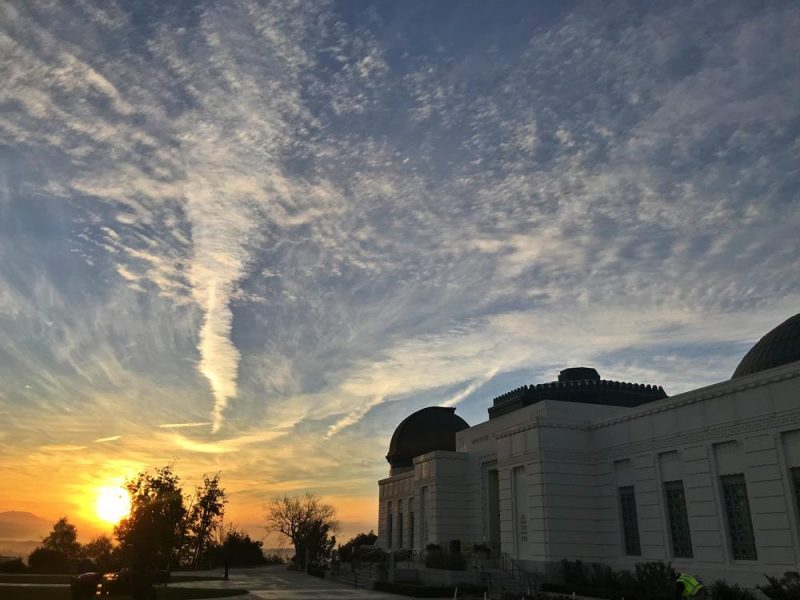 The sunrise over Griffith Observatory with fluffy clouds and blue sky