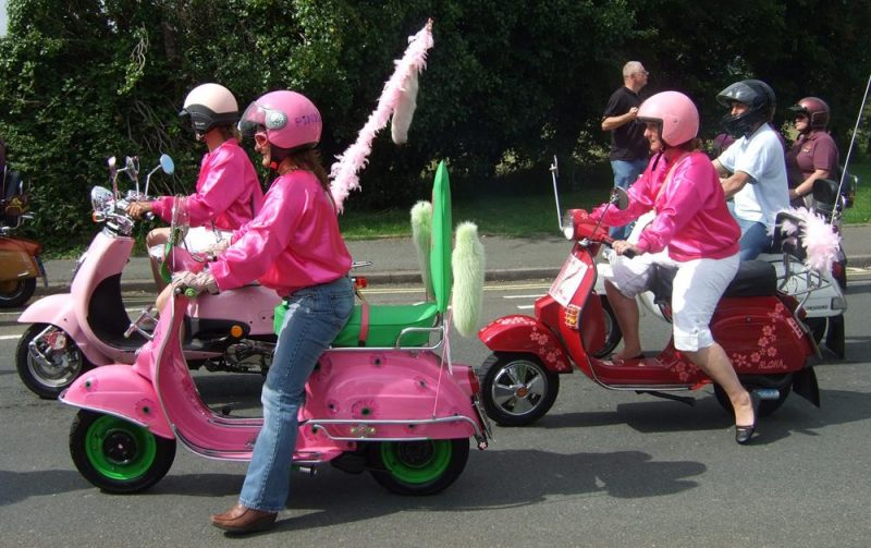 Three pink scooters with matching riders